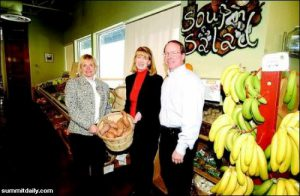 Kathy Jones, left, Anne Salisbury and Greg Meyerhoff show off produce at Alpine Natural Foods. Salisbury and Meyerhoff helped Jones make Alpine more profitable by clearing the clutter and negative energy in her store.