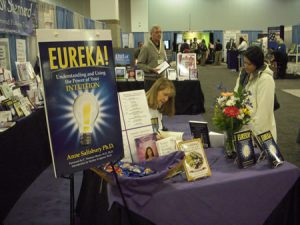 Anne Salisbury, PhD signing more books by the Eureka! sign at the American Library Association (ALA) conference in Denver, Colorado 2009.